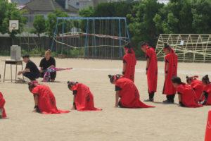 最初の出し物のソーラン隊のダンス。お揃いの赤い衣装に身を包んだメンバーがスタンバイしています。3人のメンバーがうつむき加減に立ち、その後ろにひざまずいて頭を下げている子どもたちが写っています。
