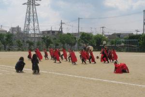 勇壮なソーラン隊のダンスの様子が写っています。お揃いの赤い衣装に身を包み、力強く踊っています。