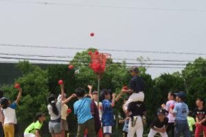変則玉入れです。みんな一生懸命に赤いカゴに向けて、赤い玉を投げ込んでいます。カゴのすぐ近くに肩車をした人がいて、赤い玉を受け取って投げようとしています。