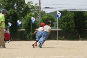 デカパン競争の様子。青のパンツのペアが折り返し地点を示す旗を今まさにまわろうとしています。
