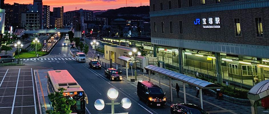 宝塚駅前のロータリー。夕闇の中バスや車が何台か停車している。わずかに見える空は紅くグラデーションになっている。