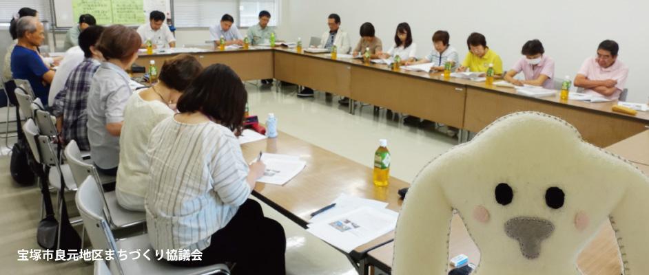 良元コミュニティ「安全な道路環境整備」勉強会での様子。口の字型に並べた机に18人ほどが座っており、資料を見ながら話を進めている。右側に大きめにまちキョンのぬいぐるみの顔が写っている。