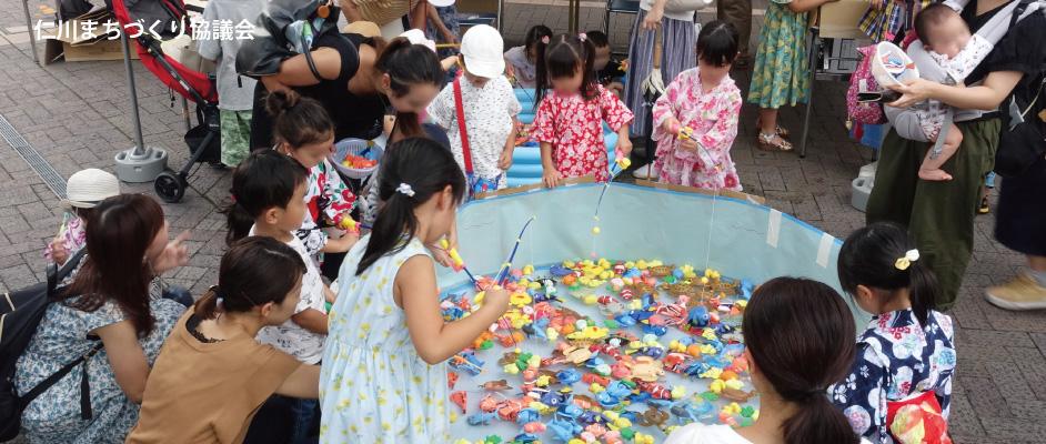 仁川まちづくり協議会での夏祭りでの様子。簡易プールの中にたくさんのお魚型などのおもちゃが入っており、その周りに小さな子どもたちとそのお母さんたちが集まっている。子どもたちは簡易な釣竿でおまちゃを釣り上げようとしている。