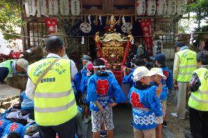お神輿の前でこども神輿のスタートを待つ子供たち。パトロールのベストを着た見守り隊の大人の方々もいます