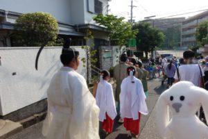 神主さんと子供の巫女さんもこども神輿に続いて歩いています。それを眺めるまちキョン。