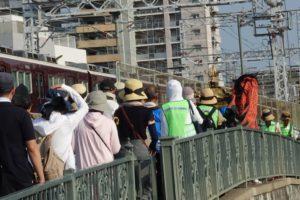 阪急電車が走る横をこども神輿が通っています。大人たちが後を続いていってます。。