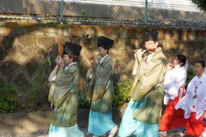 3人の神主さんがたて笛を吹きながら歩いています。子供巫女さんもそれに続きます。