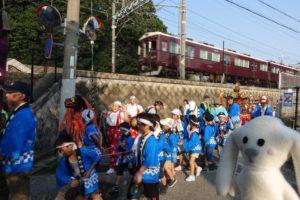 阪急電車の横を法被姿の子供たちがこども神輿をひいています。まちキョンがそれを眺めています。