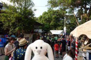 境内でのお祭りの様子をバックにうつるまちキョン。たくさん人が集まっています。