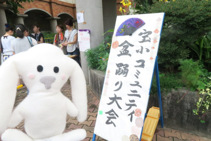 宝小コミュニティ盆踊り大会の看板の前でまちキョンが記念撮影。