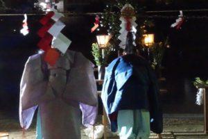 祭壇に向かって祝詞(のりと)をあげながらお辞儀をする神主さんと、そのすぐ後ろで同じようにお辞儀をする一人の巫女さん。写真の上部には赤と白の紙で作られた紙垂(しで)が垂れて厳かな雰囲気をかもしだしています。