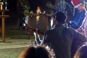 山高帽を被った洋装の男性がギターを弾く様子のアップです。