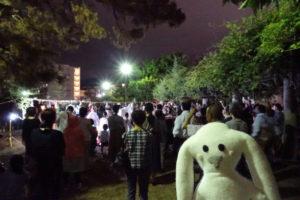 観月の夕べが行われる会場「弁天池」の前に到着したまちキョン。その背後に、準備の整った祭壇を取り囲むように、たくさんの人が舞台が始まるのを待っています。