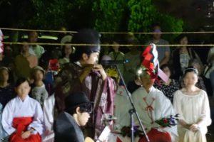 神事装束の龍笛を吹く男性のアップです。その向こうには、巫女さんたちが前に並び、その後ろに大勢の見物客の人たちが暗闇の中で聞き入っている様子が写っています。