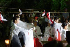 祭壇の前で、巫女さんたちが雅楽に合わせて優雅に舞を奉納する様子が写っています。
