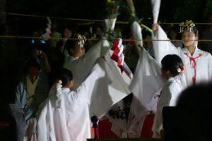舞を奉納する巫女さんたちが、右手を斜めに上げて、その上げた右手を中心にして輪のように集まっています。
