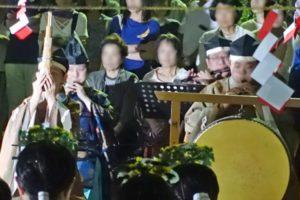 「祝詞(のりと)」に合わせて笛を吹く神事装束の人たち、その後ろには見学にきた人たちが写っています。手前右には太鼓が写っています。