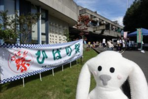 宝塚大学の入り口。左手にはひばり祭の横断幕。奥は、沢山の人でにぎわっている。右下にまちキョンが写っている