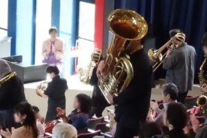 立ってトランペットなどを演奏する人と観客席に座って拍手するお客さん。