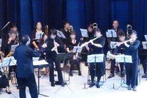 楽譜を見ながら様々な楽器を演奏する人たちと指揮者。