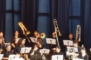 座って、楽譜を見ながらトランペットなどを演奏する10名ほどの演奏者たち。