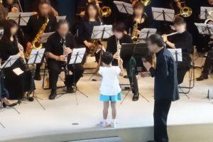 座って様々な楽器を演奏する人たちとそれを指揮する小さなこども。