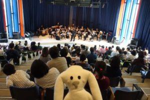 観客席に座っている大勢のお客さんとステージの上のたくさんの演奏者とステージ中央にいる一人の指揮者。中央下にまちキョンが写っている