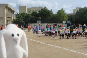 開会式が始まり、運動場には、赤や青の帽子をかぶった体操服姿の子どもたちが並んでいます。その様子を眺めるまちキョンが写真左側に写っています。