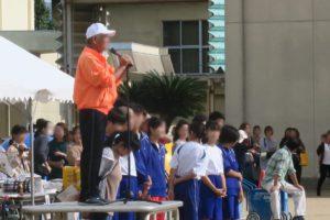 開会式で、オレンジ色のジャケットを着て、白い帽子をかぶった男の人がマイクを握って、台の上で挨拶をしているところです。