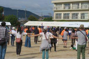 開会式の後、みんなが運動場に広がって、体をほぐすために準備体操をしている様子が写っています。