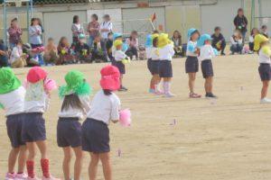 幼稚園のお友達が、体操服姿で赤や緑、青、黄色の帽子をかぶり、手には帽子とお揃いの色のポンポンを持ってダンスを踊っています。
