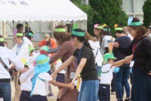 幼稚園のお友達がママやパパと一緒に手をつないで踊ってます。ママやパパは、手作りの鉢巻のような飾りを頭にかぶっています。みんな楽しそうです。