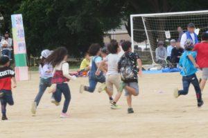 小学生の徒競走で、スタートの合図で走り出したところが写っています。みんなが懸命にダッシュしています。
