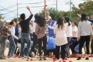 玉入れです。地面には赤い玉がいっぱい転がっています。たくさんの人がカゴに向かって玉を投げ入れようと頑張っている様子が写っています。