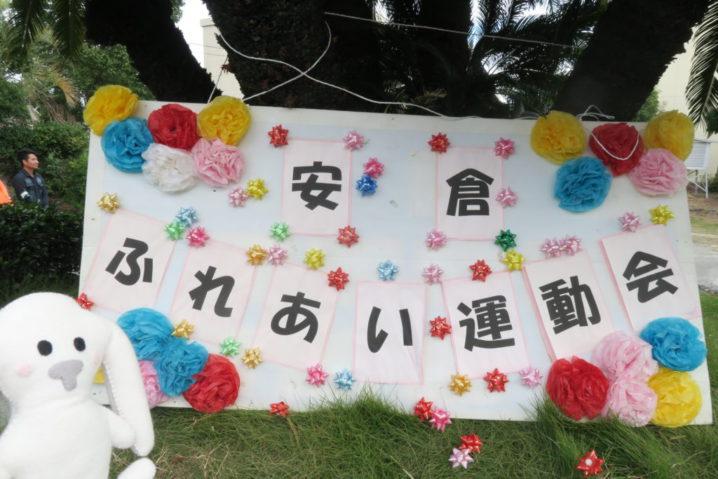安倉ふれあい運動会の会場、安倉小学校に到着したまちキョン、手作り感いっぱいの「安倉ふれあい運動会」の看板を斜め後ろにして、芝生の上にちょこんと座ってポースをとっています。