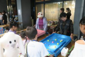 スマートボールで遊ぶ子どもたちと運営の女性。左下にまちキョンが写っている。