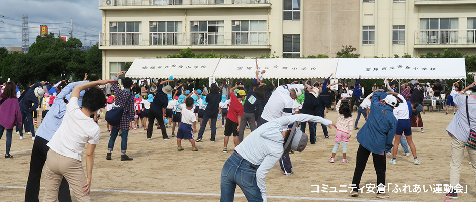 コミュニティ安倉で行われたふれあい運動会の一幕。小学校のグラウンドに地域の方がたくさんおり、校舎の方向に向いてみんなでラジオ体操をしている。