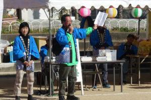 ステージの上に青い法被を着た男性と女性が立っています。男性がマイクを右手に握り、プログラムを持ったもう左手を横に広げ、話をしています。