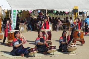 ステージで行われている和太鼓の演奏の様子です。赤い法被を着ている子どもたちが、ちょうどバッチを高く振り上げたところが写っています。次の瞬間、ドンドンドンと音が聞こえてきそうです。