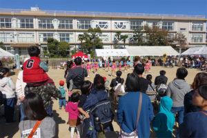 奥の校舎を背景に舞台があり、舞台を遠巻きに観ているまちの人たちの後ろ姿が写っています。子ども連れの人や、小さな子どもを肩車している人もいます。舞台ではピンク色の衣装を着た子どもたちが踊っている様子が遠く小さく写っています。