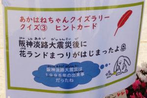 赤い羽根の「あかはねちゃんクイズラリー」のクイズ③のヒントカードが写っています。「阪神淡路大震災後に花ランドまつりがはじまったよ」と書かれていて、その下にまちキョンのつぶやき「阪神淡路大震災は1995年の出来事だったね」と書かれています。