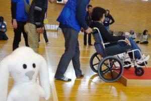 小学校のアリーナ(体育館)での車椅子体験の様子です。女性の方が乗っている車椅子を、青いスタッフジャケットを着た男性が、段差のあるところを押してあがろうとしています。周りでその様子をみんなが見ています。左側の隅にその様子を見ているまちキョンがいます。