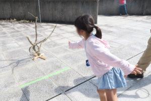 木でつくられた輪投げで遊ぶ女の子。