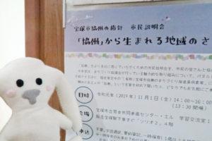 「宝塚市協働の指針 市民説明会」の会場に到着したまちキョン。『「協働」から生まれる地域のささえあい』と書かれたポスターの前に立っています。