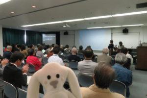 今まさに「宝塚市協働の指針 市民説明会」が開かれている会場内にまちキョンが入りました。会場内では、たくさんの人が説明を聞いています。まちキョンも後ろの方からそっと参加です。
