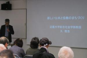 写真の向かって左側に近畿大学の久(ひさ)先生、右側にはプロジェクタに映し出された文字「新しい公共と協働のまちづくり 近畿大学総合社会学部教授 久 隆浩(ひさ たかひろ)」が映し出されています。