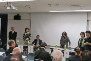 活動事例の発表になり、発表者が前に出てきたところです。前の方には、男性や女性が何人か立っているのが写っています。近畿大学の久先生の姿もあります。