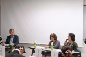 活動事例の発表の様子です。向かって左側から近畿大学の久先生、少し離れて事例発表の2人の女性が机を前にして座っています。2人の女性のうち、右側の女性がマイクを持って発表しています。