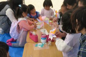 工作のブースの様子です。かわいい子どもたちが風車を作っています。お母さんに抱っこされながら一生懸命作っている子もいます。机の上にはセロテープや、サンプルの風車が置いてあります。風車はピンクやオレンジ、薄紫ととてもやさしい色です。