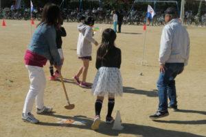 運動場で行われているゲートボールの様子です。旗のある方に向かってボールを打つ親子連れと、それを指導している年配の男性が写っています。